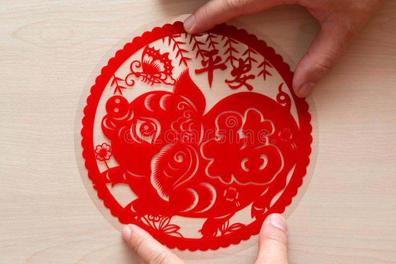 Sticking fluffy red flat paper-cut sticker as symbol of Chinese New Year of the pig the Chinese means the pig brings you safety. Sticking a fluffy red flat paper stock photography