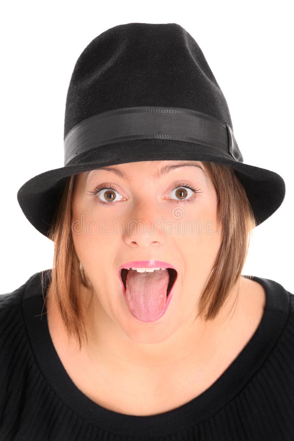 Sticking out tongue. A portrait of a pretty young woman in a black hat sticking out tongue over white background royalty free stock images
