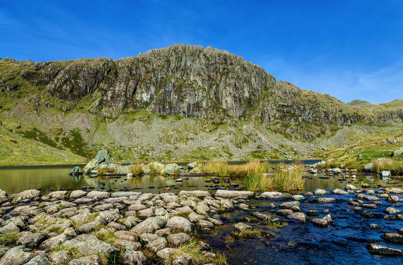 Stickle Tarn and Pavey Ark. A view of Stickle Tarn and Pavey Ark in the English Lake District stock images