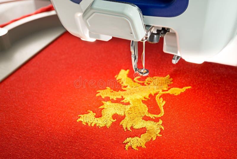 Stickmaschine- und Goldlöwe entwerfen auf rotem Baumwollgewebehemd, Abschluss herauf Bild stockfotografie