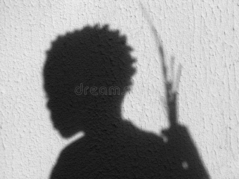Shadow of a boy holding sticks on stone royalty free stock photos