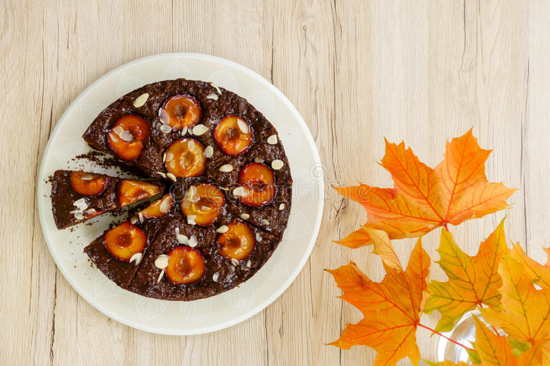 Sticky Chocolate Plum Cake with Autumn Decoration. Homemade Sticky Chocolate Plum Cake with Chestnut Leaves as Autumn Decoration. Shot directly from above. On royalty free stock image