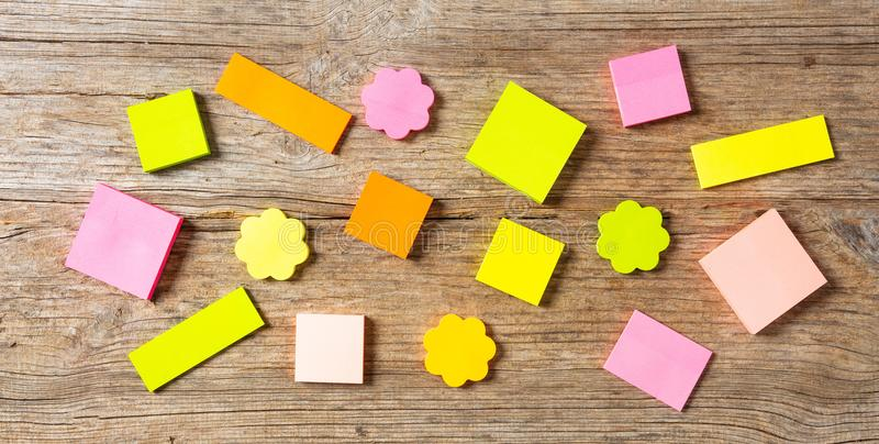 Sticky colorful notes in various shapes, isolated, copy space on wooden background. stock photos