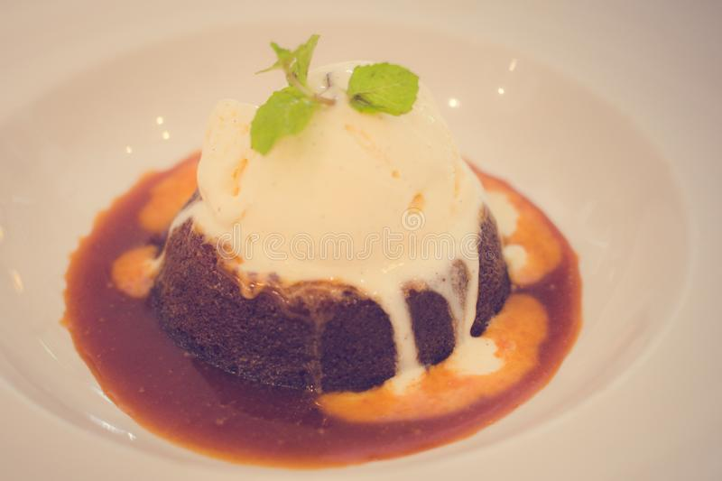 Sticky date pudding Salted caramel sauce vanilla bean ice-cream. Sticky date pudding Salted caramel sauce & vanilla bean ice-cream royalty free stock images