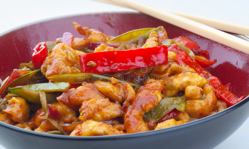 Sticky lemon chicken with peppers and mange tout royalty free stock photos