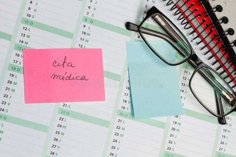 Sticky note and eyeglasses on a calendar. Sticky note with cita medica text and eyeglasses on a calendar stock image