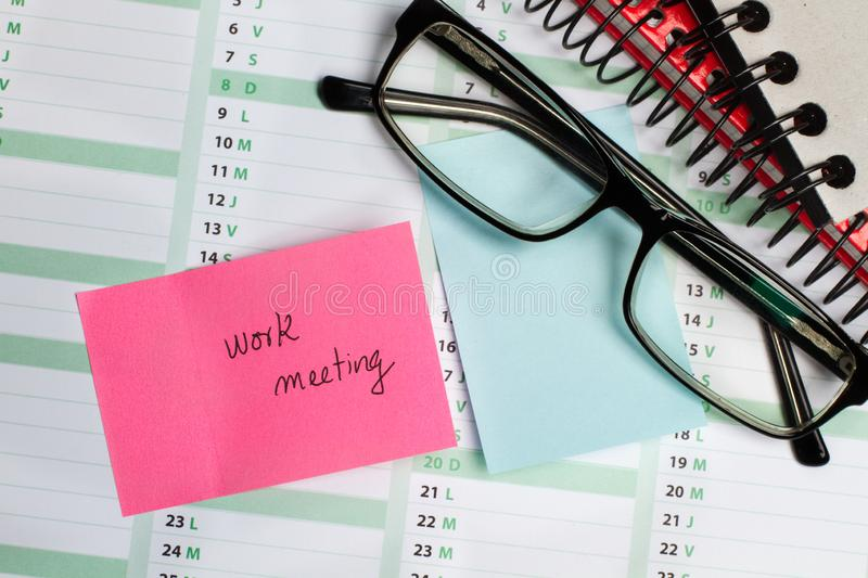 Sticky note and eyeglasses on a calendar. Sticky note with work meeting text and eyeglasses on a calendar stock photos