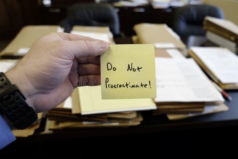 Sticky Note in Hand Businessman Desk Files Folder Working Do Not Procrastinate. Sticky Note in Hand Businessman Desk Files Folder Working Message Motivation Do stock photos