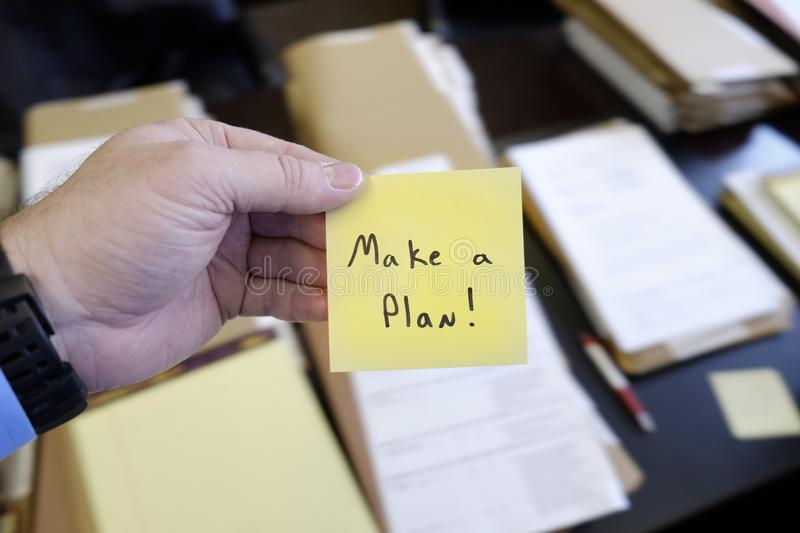 Sticky Note in Hand Businessman Desk Files Folder Working Make a Plan. Sticky Note in Hand Businessman Desk Files Folder Working Message Motivation Make a Plan royalty free stock photography