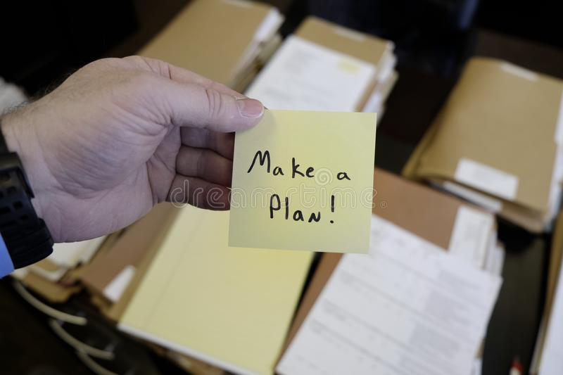 Sticky Note in Hand Businessman Desk Files Folder Working Make a Plan. Sticky Note in Hand Businessman Desk Files Folder Working Message Motivation Make a Plan stock photos