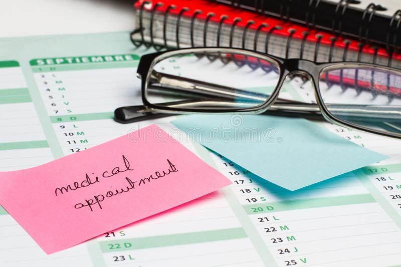 Sticky note and eyeglasses on a calendar. Sticky note with medical appointment text and eyeglasses on a calendar stock photos