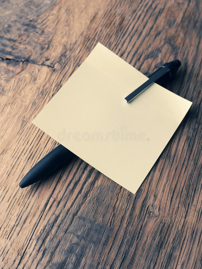 Sticky note with a pen on a table. Close up shot, high angle view royalty free stock photo