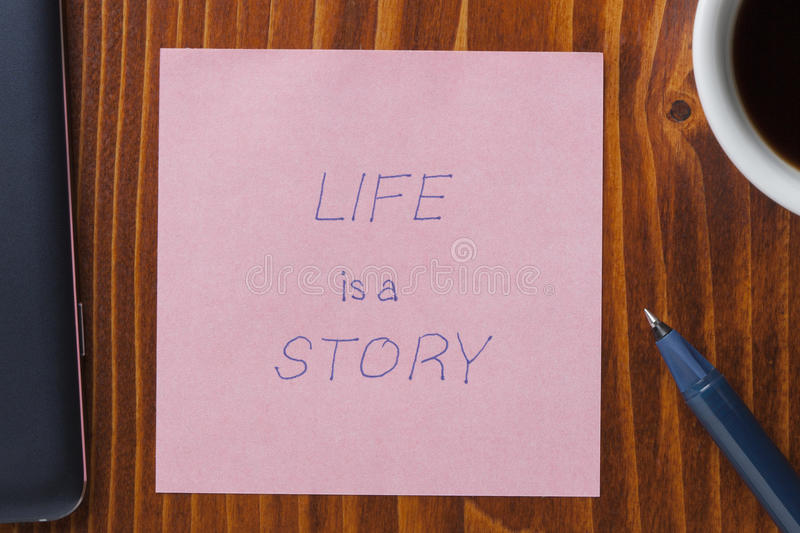 Sticky note with tex life is a story. Life is a story handwritten text on a note with pen royalty free stock photo