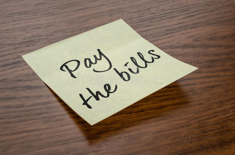 Sticky note with the text Pay the bills stock photography