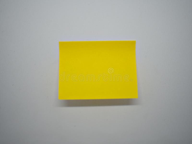 Sticky note on the white background. Sticky note stick on the isolated white wall with a small shadown under it stock image