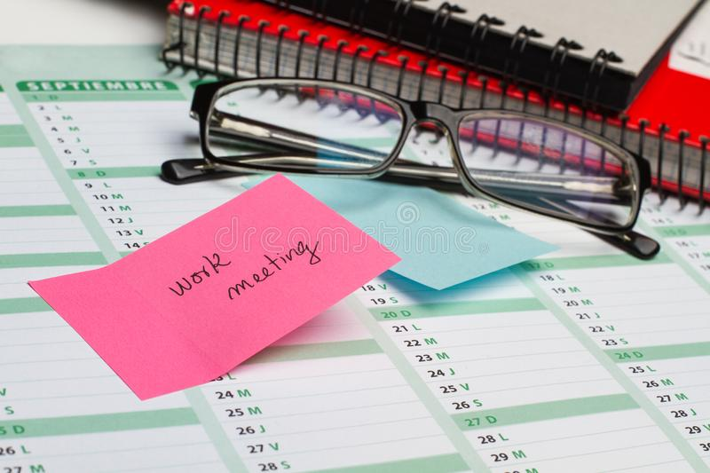 Sticky note and eyeglasses on a calendar. Sticky note with work meeting text and eyeglasses on a calendar royalty free stock image