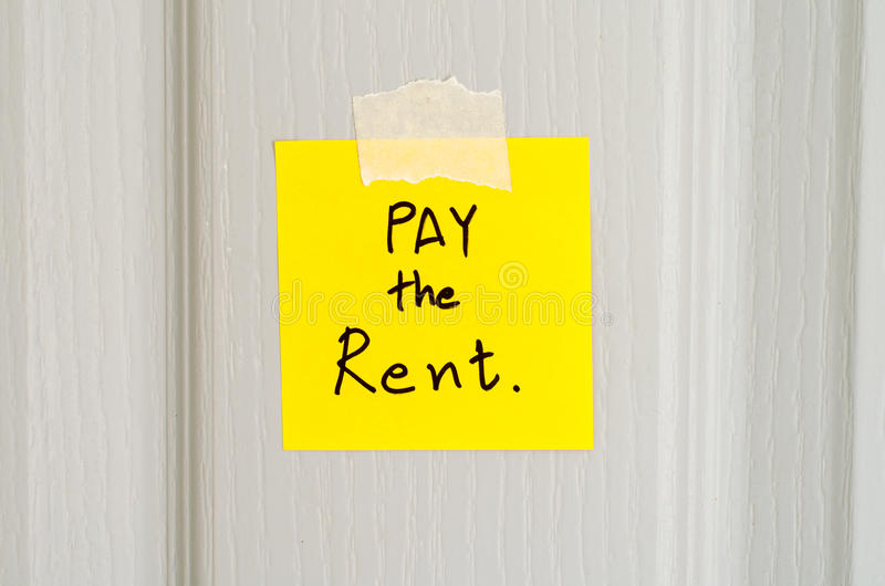 Sticky note write a message pay the rent. On wood door background royalty free stock photography