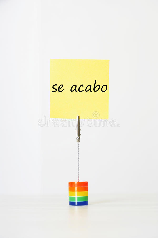 Sticky notepaper with Spanish text se acabo (It s over) clipped to a multicolored card holder