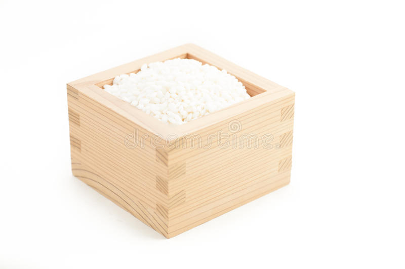 Sticky rice in Japanese sake cup called Masu. On white isolated background royalty free stock images