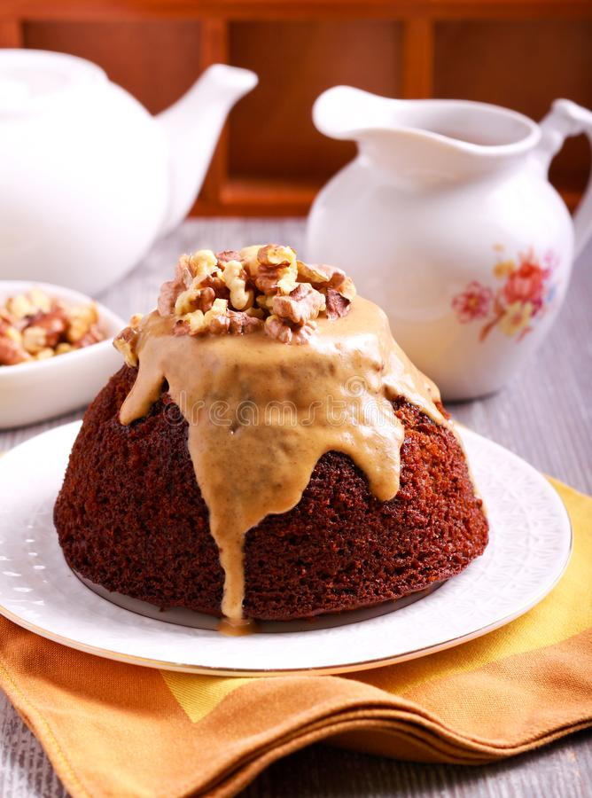 Sticky toffee pudding with caramel sauce. And nuts royalty free stock image