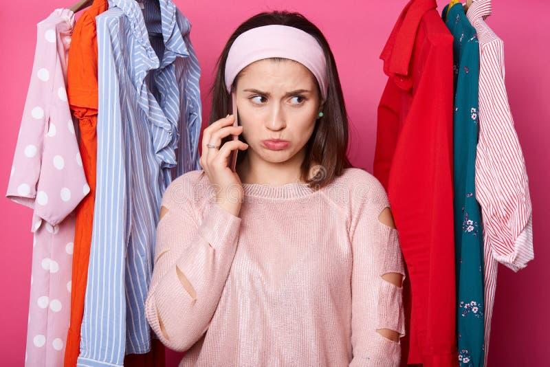 Stidio射击了年轻女人发表演讲关于手机和选择衣裳在商店,没有足够的金钱,告诉她的丈夫并且要求 免版税库存图片