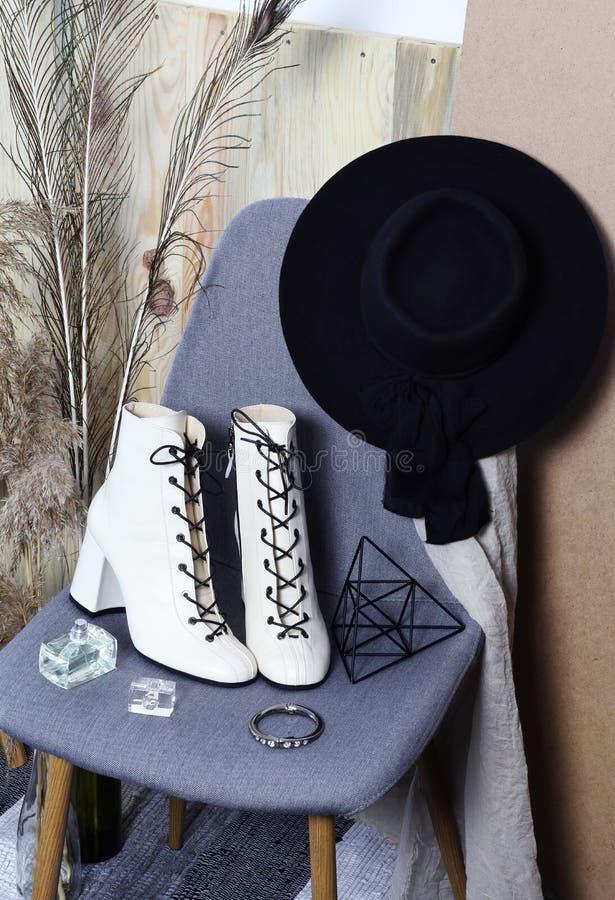 Stiefel der weißen Frauen der Mode und schwarzer Hut auf dem Stuhl lizenzfreie stockbilder