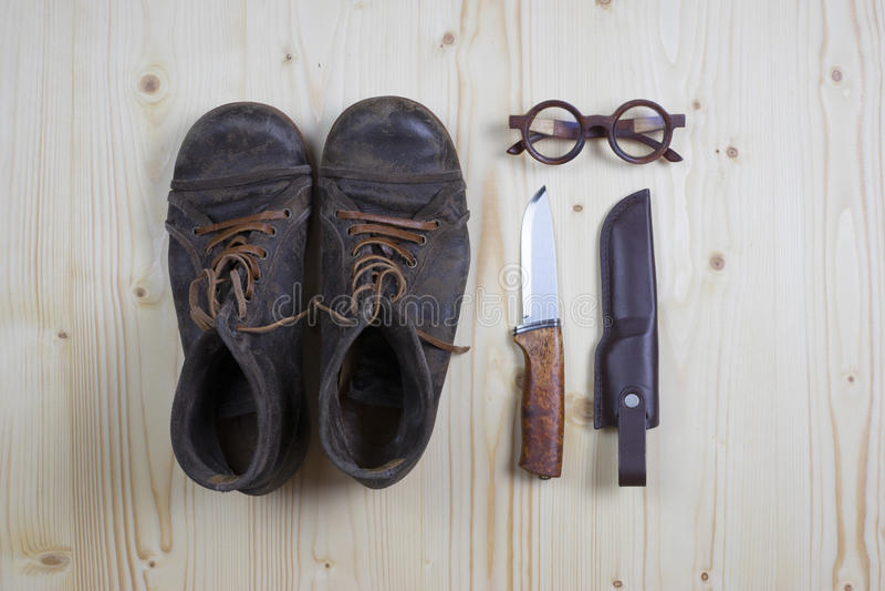 Stiefel und Messer auf Kiefernholz lizenzfreies stockfoto