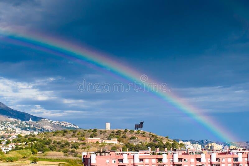 Stier-Statue und ein Regenbogen stockfotos