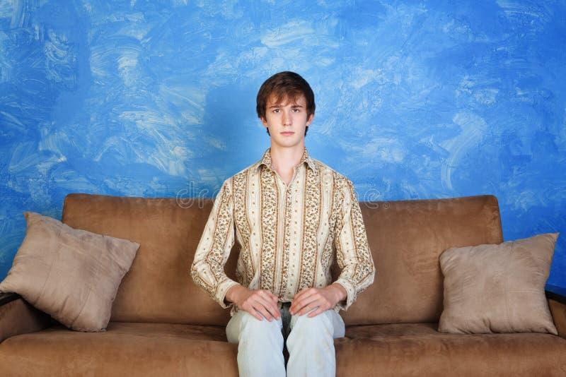 Stiff Young Man on Sofa royalty free stock image