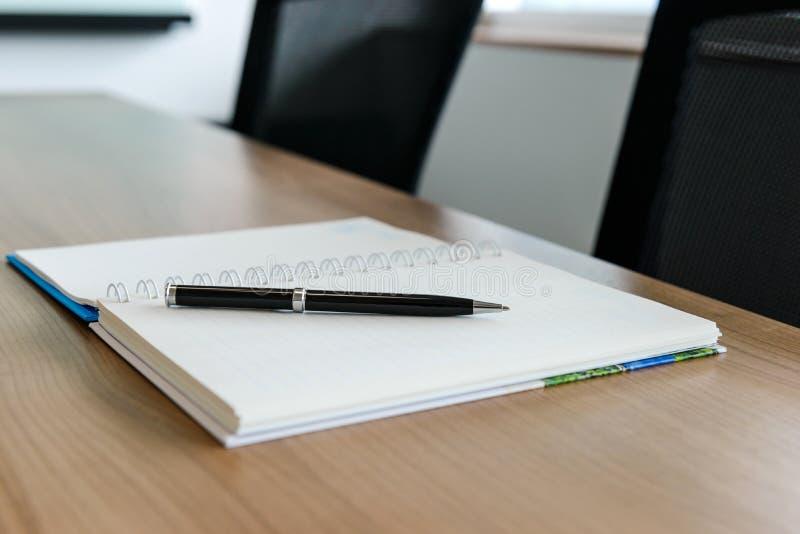 Stift auf Notizblock für Tagesordnung hielt auf Tabelle im Unternehmenskonferenzsaal lizenzfreie stockfotografie