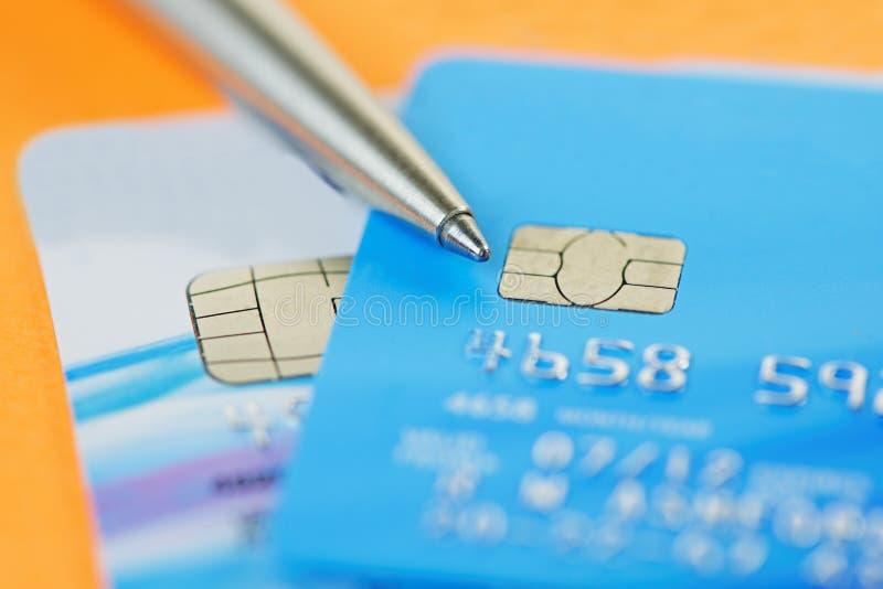 Stift und Kreditkarten auf einem orange Notizblock stockbilder