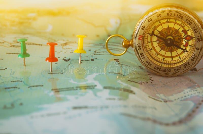 Stifte befestigt zur Karte, Standort oder Reiseziel und alter Kompass zeigend stockbild