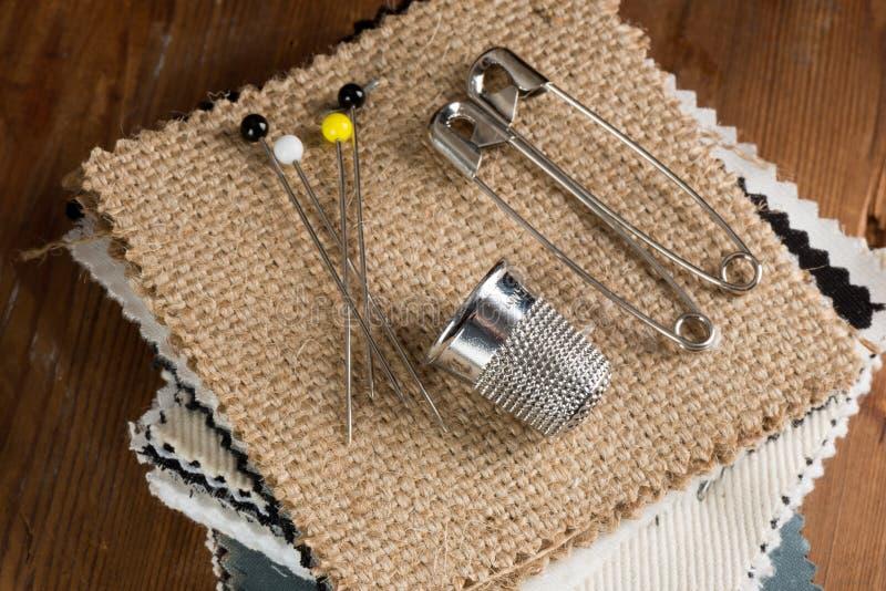 Stifte und Muffe auf Stapel von Gewebe-Mustern stockbilder