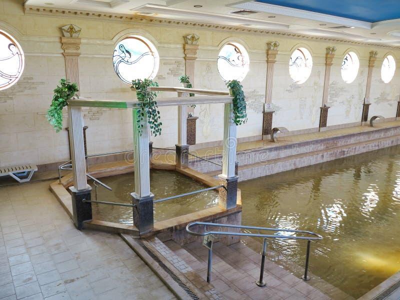 Stig ned till pölen med varmt termiskt vatten och en separat bubbelpool i den inomhus paviljongen av den vila satsen Zhaivoronok fotografering för bildbyråer