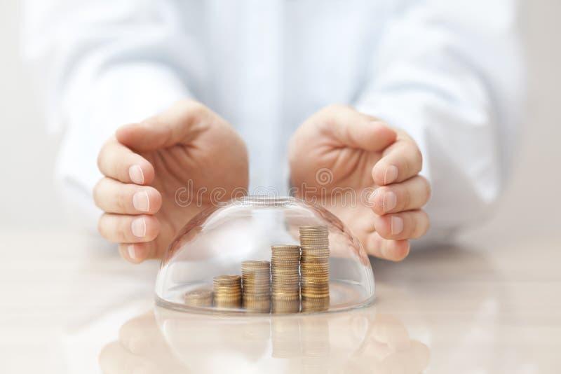Stigande mynt som skyddas under en glass kupol och händer arkivfoton