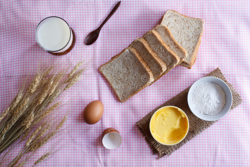 Stiil liv med bröd-, ägg-, magarine-, mjöl- och vetenolla för helt vete royaltyfri foto