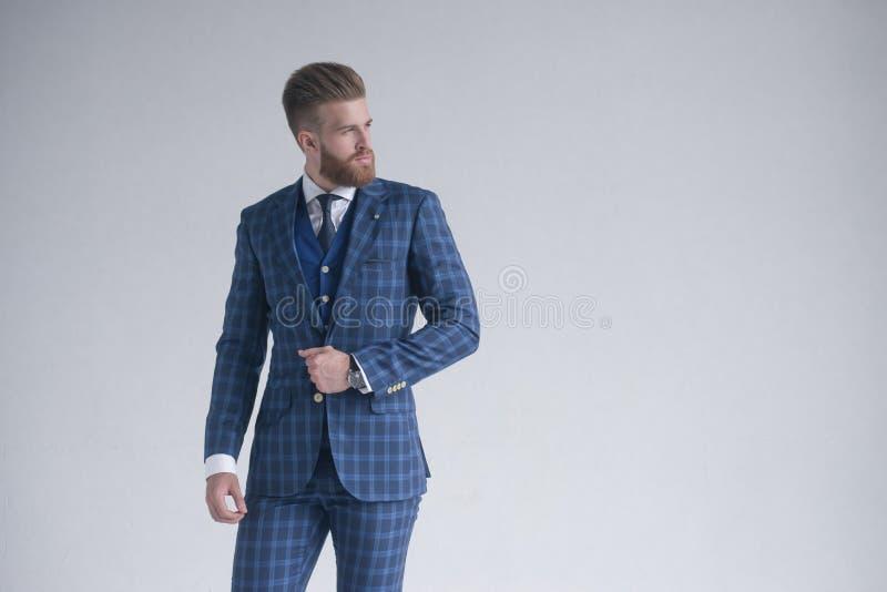 Stijl in motie Knappe jonge mens in drie-stuk kostuum het stellen voor grijze achtergrond stock foto's
