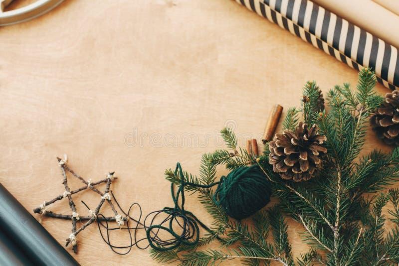 Stijlvol verpakkingspapier, houten ster, pijnboomtakken en kegels, draad op houten tafel op het platteland, kopieerruimte Rustige stock foto's