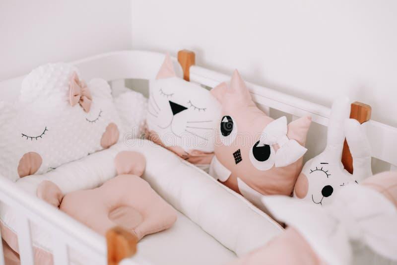 Stijlvolle babykamer met comfortabele kribbe. Kinderslaapkamer in scandinavische stijl met gekleurde decoratieve kussens stock afbeeldingen