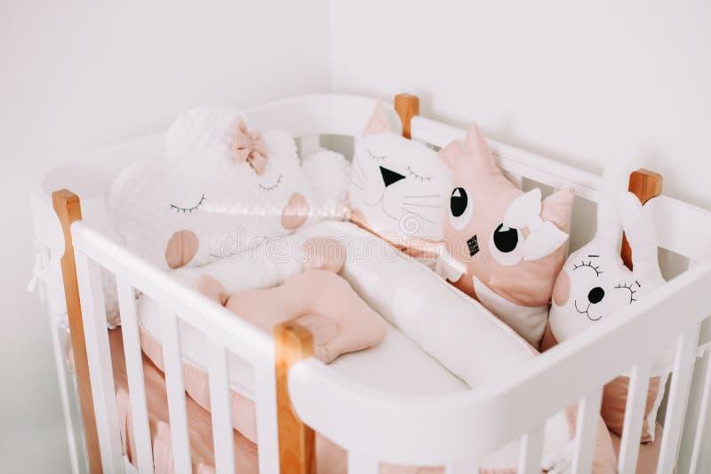 Stijlvolle babykamer met comfortabele kribbe. Kinderslaapkamer in scandinavische stijl met gekleurde decoratieve kussens stock fotografie