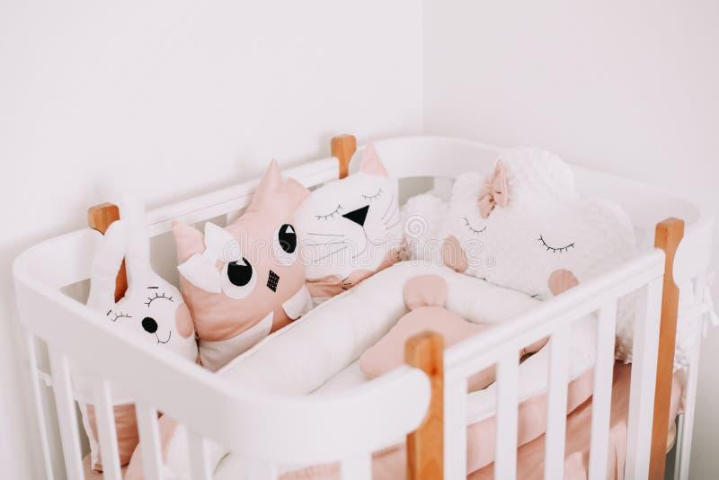 Stijlvolle babykamer met comfortabele kribbe. Kinderslaapkamer in scandinavische stijl met gekleurde decoratieve kussens stock foto's