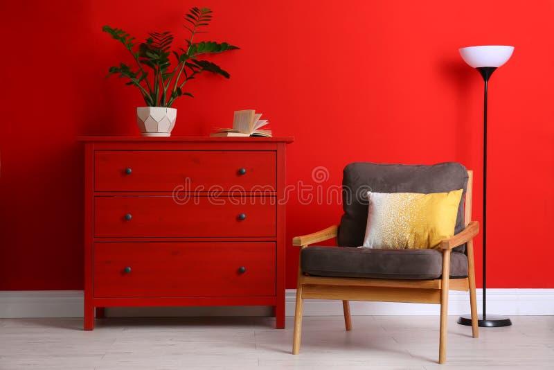Stijlvolle kamer binnenshuis met meubilair en woonkamer bij rode muur stock fotografie