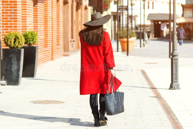 Stijlvolle vrouw die op straat loopt. Meisje met rode jas, zwarte hoed en trendy tas. Mode outfit, najaarstrend, stock foto