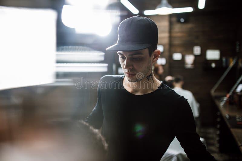 Stil för man` s Modebarberaren gör en stilfull frisyr för enhaired man som sitter i fåtöljen i det stilfullt fotografering för bildbyråer