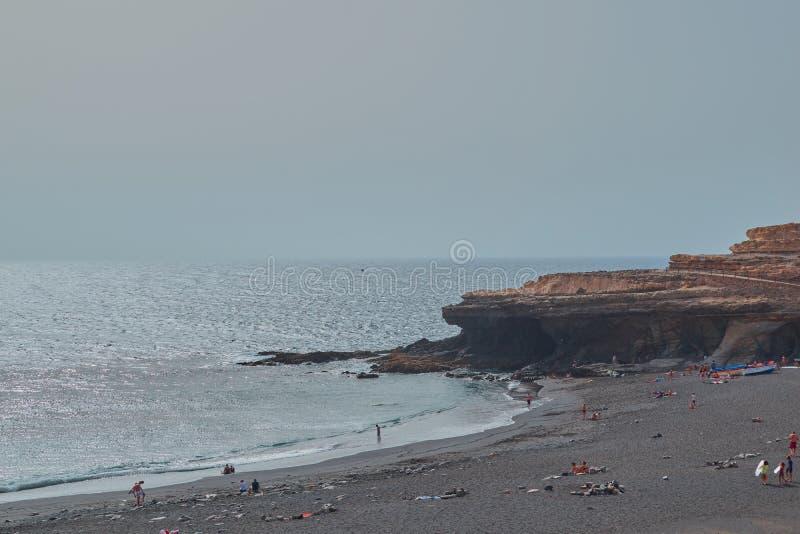 Stil strand die in Ajuy met en mensen vissen die, Fuerteventura baden zonnebaden royalty-vrije stock afbeelding