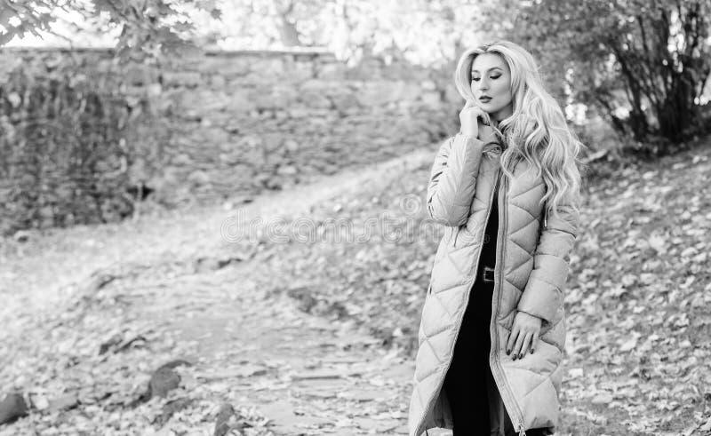 Stile casuale e comodo del rivestimento della soffiatore Passeggiata bionda alla moda della ragazza nel parco di autunno La donna fotografia stock