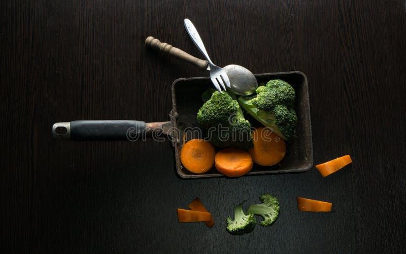 Stile dell'alimento delle carote e dei broccoli in vecchia pentola sulla tavola di legno nera fotografia stock libera da diritti