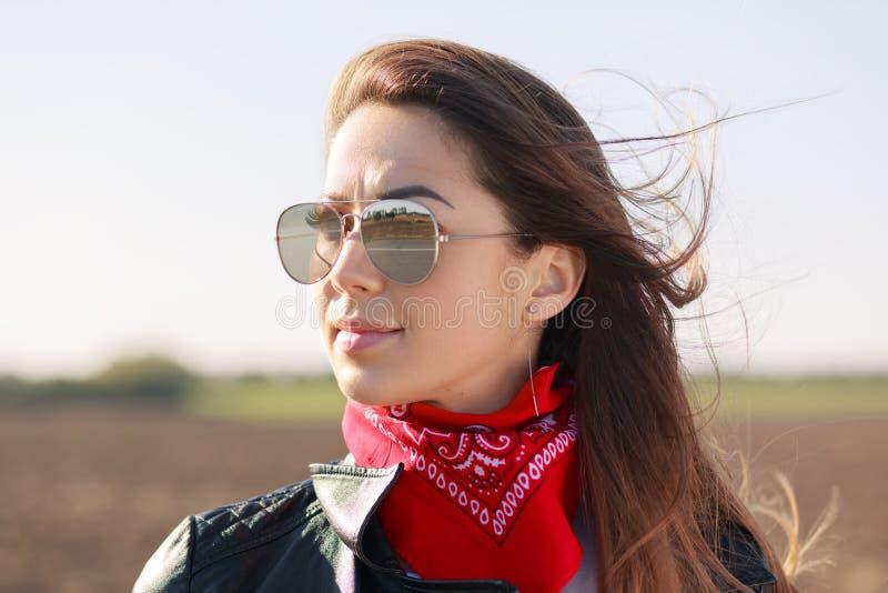 Stile della roccia Chiuda sul colpo della donna premurosa mora vestita in bomber, bandana rossa ed occhiali da sole, messi a fuoc immagini stock