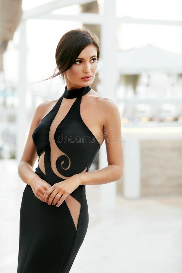 Stile delle donne Ragazza di modo in vestito nero lungo che posa all'aperto fotografia stock