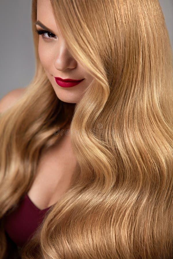 Stile di capelli Bella donna con capelli biondi lunghi ondulati sani immagine stock